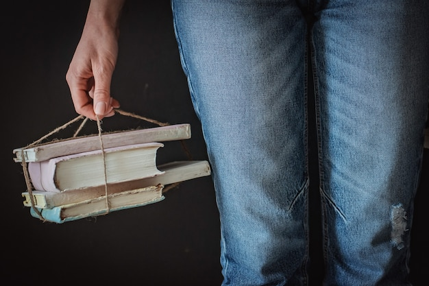Jeune fille hipster lit un livre à la maison. formation, l'étudiant se prépare à l'examen. vieux livre rareté antique. jeans minables livres