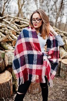 Jeune fille hipster porter sur la couverture et des lunettes contre des souches en bois sur bois.