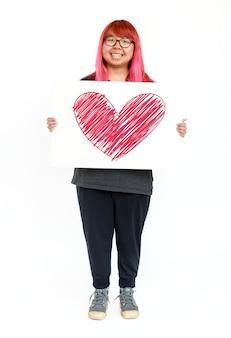 Jeune fille hipster tenant icône coeur à bord
