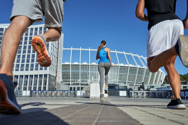 Jeune fille et hommes en tenue sportive courant vers le stade