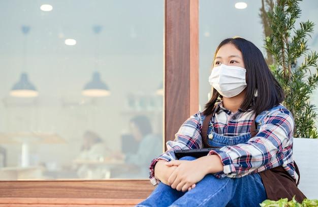 Jeune fille a une humeur triste avec un client en attente devant la porte du café en raison d'une infection virale