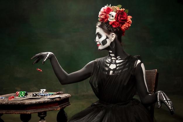 Jeune fille à l'image de santa muerte, saint mort ou crâne de sucre avec un maquillage lumineux.