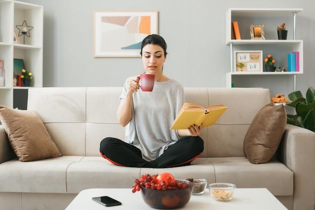 Jeune fille impressionnée tenant une tasse de thé lisant un livre dans sa main assise sur un canapé derrière une table basse dans le salon