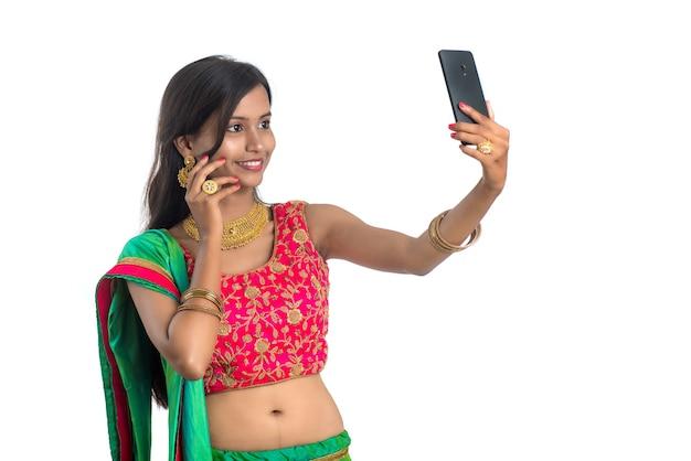 Jeune fille indienne à l'aide d'un téléphone mobile ou d'un smartphone sur blanc