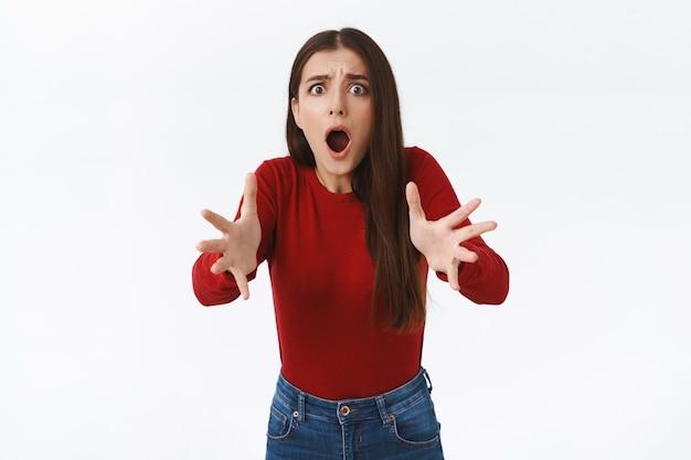 Jeune fille inquiète choquée regardant quelqu'un en danger, haletant effrayé debout stupéfait, demandant de faire attention, écartant les mains pour aider quelqu'un, pose un fond blanc alarmé