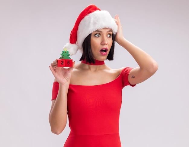 Jeune fille inquiète portant un bonnet de noel tenant un jouet d'arbre de noël avec la date en gardant la main sur la tête en regardant de côté isolé sur fond blanc