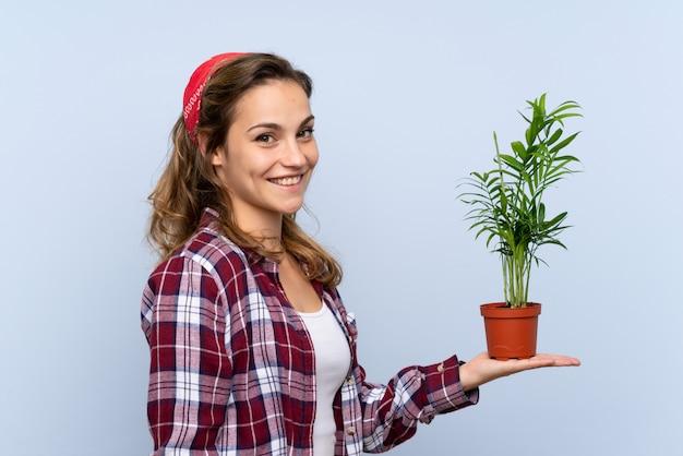 Jeune fille de jardinier blonde tenant une plante sur un mur isolé
