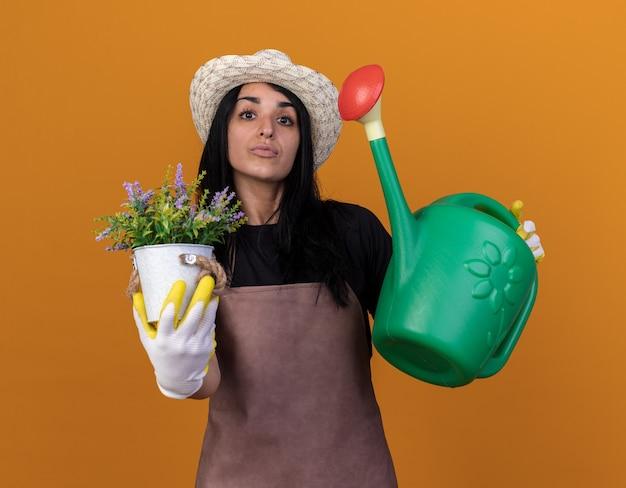 Jeune fille de jardinier caucasienne confiante portant un uniforme et un chapeau avec des gants de jardinier tenant un arrosoir et un pot de fleurs isolé sur un mur orange