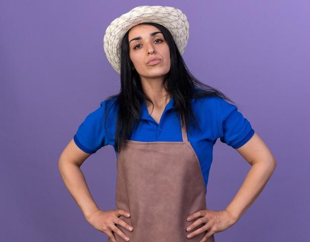 Jeune fille de jardinier caucasienne confiante en uniforme et chapeau gardant les mains sur la taille isolée sur un mur violet
