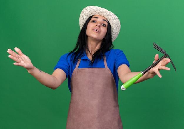 Jeune fille de jardinier impressionnée en uniforme et chapeau tenant un râteau-houe regardant devant tendant la main vers l'avant isolé sur un mur vert