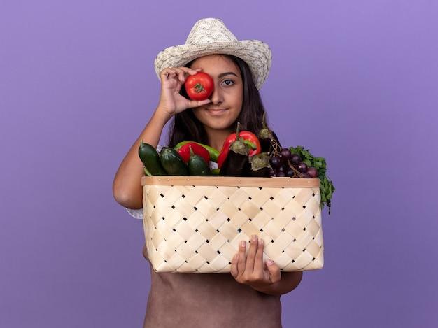 Jeune fille de jardinier en tablier et chapeau d'été tenant une caisse pleine de légumes couvrant son œil avec des tomates fraîches debout sur un mur violet