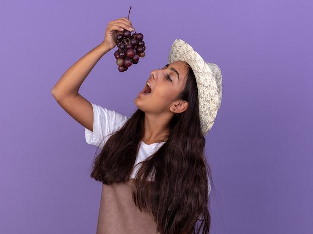 Jeune fille de jardinier en tablier et chapeau d'été tenant grappe de raisin sur sa bouche va goûter debout sur le mur violet