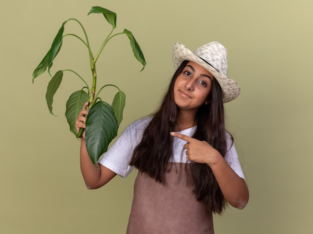 Jeune fille de jardinier en tablier et chapeau d'été tenant la plante pointant avec l'index sur elle souriant debout sur mur vert