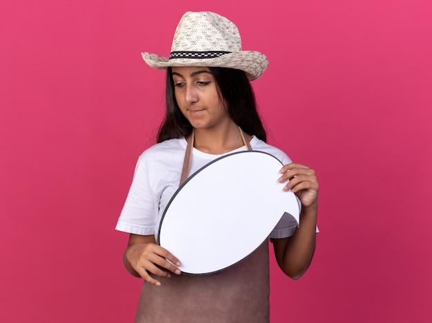 Jeune fille de jardinier en tablier et chapeau d'été tenant un signe de bulle de discours vide à côté avec un visage sérieux debout sur un mur rose