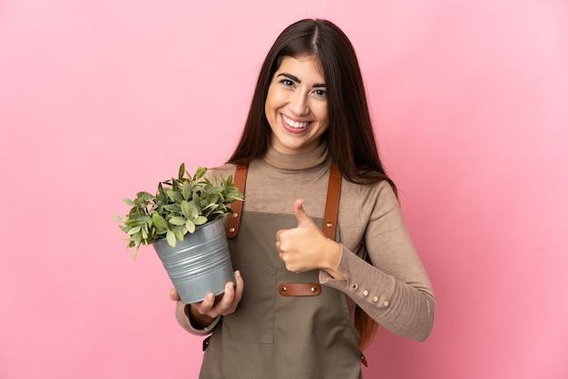 Jeune fille de jardinier tenant une plante isolée sur fond rose donnant un geste du pouce vers le haut