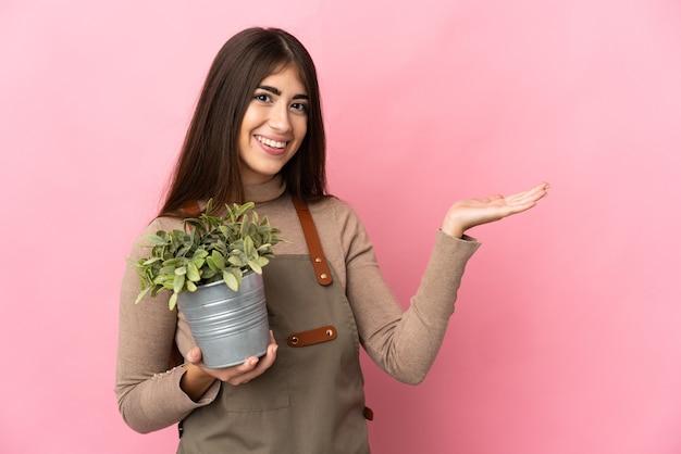 Jeune fille de jardinier tenant une plante isolée sur fond rose étendant les mains sur le côté pour inviter à venir