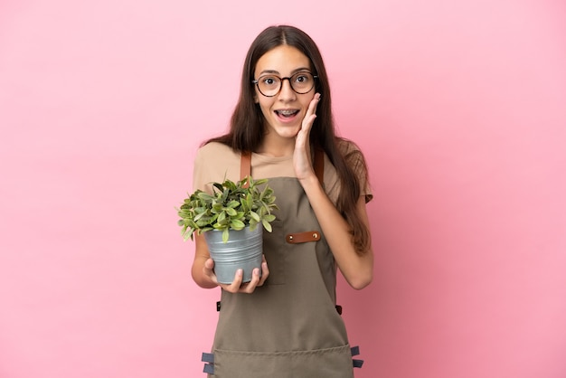 Jeune fille de jardinier tenant une plante isolée sur fond rose avec une expression faciale surprise et choquée