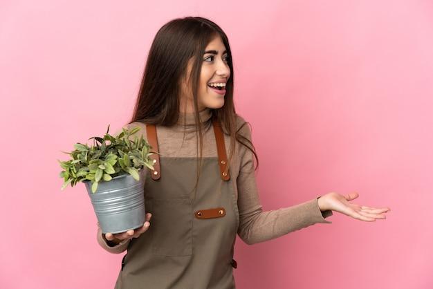 Jeune fille de jardinier tenant une plante isolée sur fond rose avec une expression de surprise tout en regardant de côté