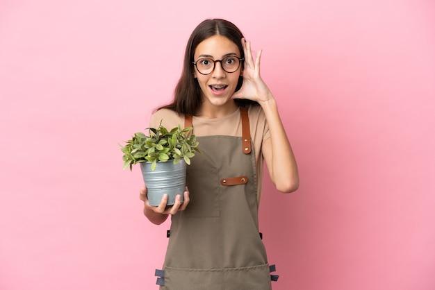 Jeune fille de jardinier tenant une plante isolée sur fond rose avec une expression de surprise