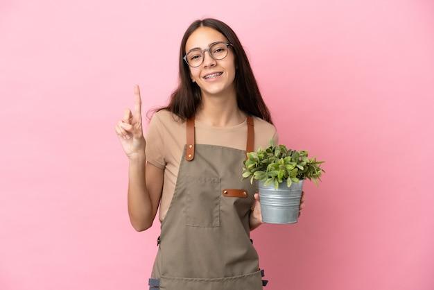 Jeune fille de jardinier tenant une plante isolée sur fond rose montrant et levant un doigt en signe du meilleur