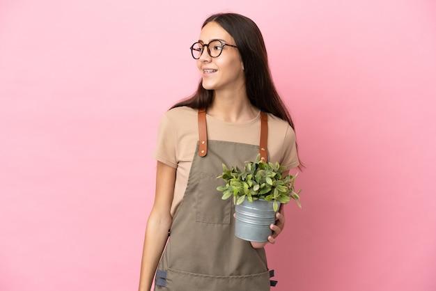 Jeune fille de jardinier tenant une plante isolée sur fond rose regardant sur le côté et souriant