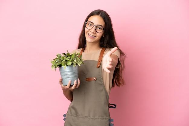 Jeune fille de jardinier tenant une plante isolée sur fond rose se serrant la main pour conclure une bonne affaire