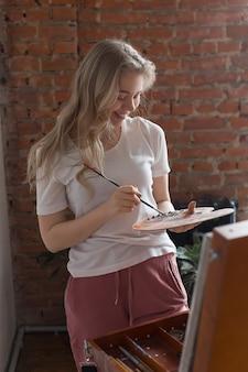 Jeune fille jolie blonde souriante avec pinceau, mélange de couleurs dans la palette