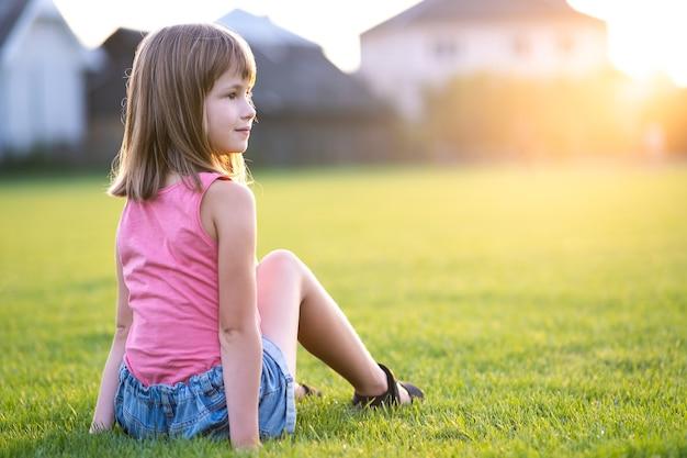 Jeune fille jolie enfant assis sur l'herbe verte fraîche.