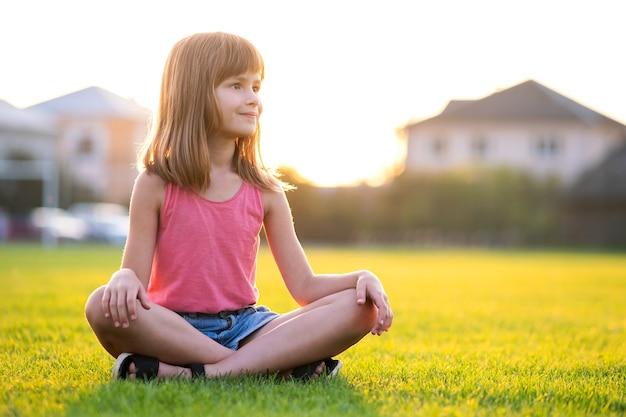 Jeune fille jolie enfant assise sur la pelouse d'herbe verte fraîche sur une chaude journée d'été à l'extérieur.