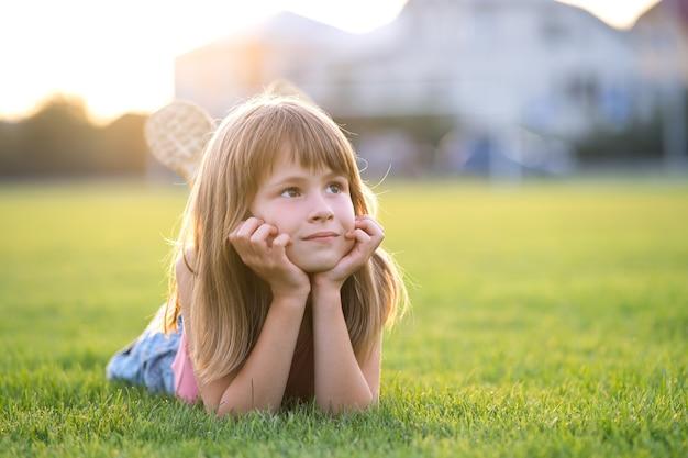 Jeune fille jolie enfant fixant sur la pelouse d'herbe verte sur une chaude journée d'été.
