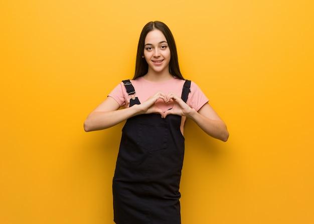 Jeune fille jolie naturelle faisant une forme de coeur avec les mains