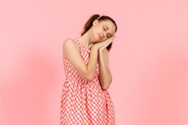 Jeune fille en jolie robe lumineuse se sentir fatigué et essayer de dormir sur rose