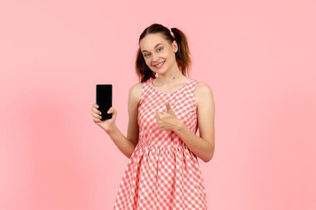 Jeune fille en jolie robe lumineuse tenant le téléphone rose