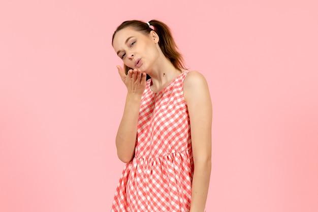 Jeune fille en jolie robe rose envoi de baisers aériens sur rose