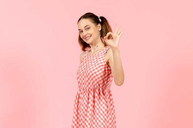 Jeune fille en jolie robe rose avec une expression souriante sur rose