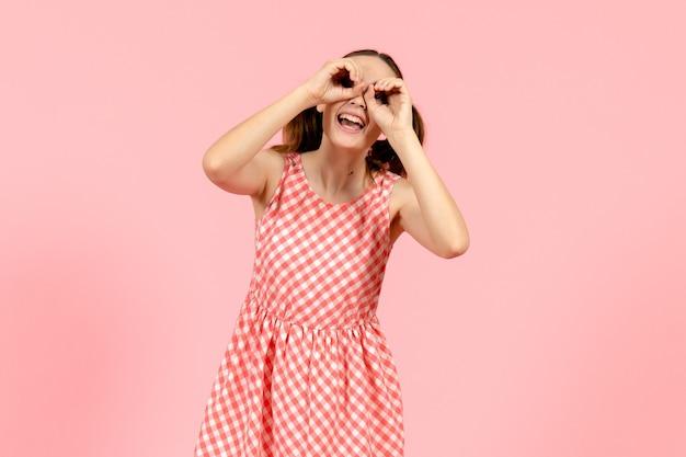 Jeune fille en jolie robe rose regardant à travers ses doigts sur rose