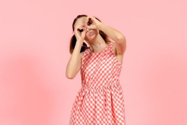 Jeune fille en jolie robe rose sur rose