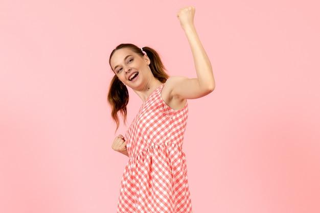 Jeune fille en jolie robe rose se réjouissant émotionnellement sur rose