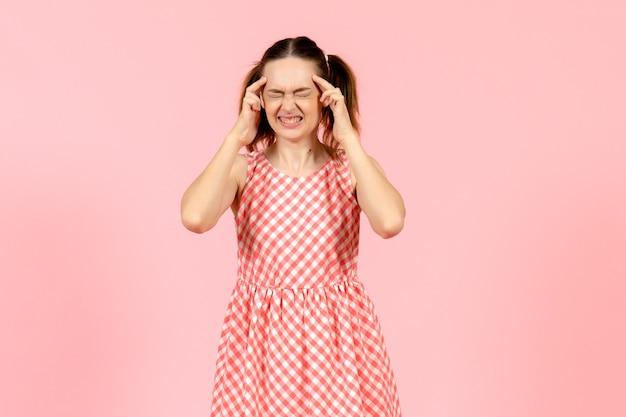 Jeune fille en jolie robe rose souffrant de maux de tête sur rose