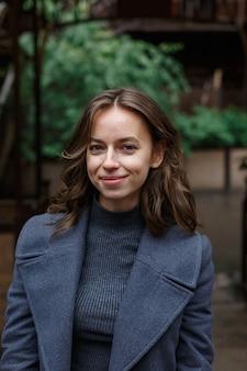 Jeune fille jolie souriante heureuse en manteau gris et col roulé pose à l'extérieur
