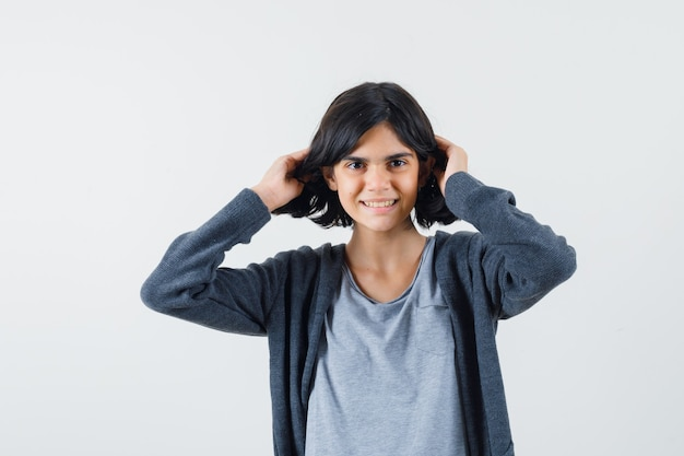Jeune Fille Jouant Avec Les Cheveux En T-shirt Gris Clair Et Sweat à Capuche Zippé Gris Foncé Et à La Jolie. Photo gratuit