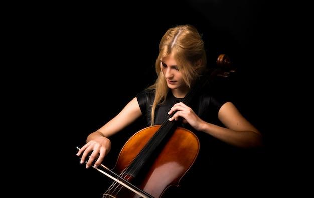 Jeune fille jouant du violoncelle sur fond noir isolé