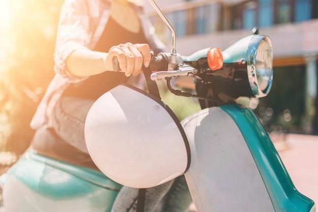 Jeune fille joyeuse au volant de scooter en ville. portrait d'une femme jeune et élégante avec un cyclomoteur