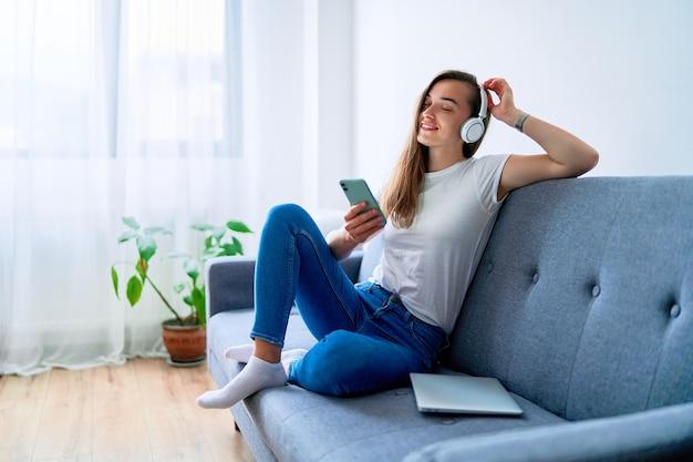 Jeune fille joyeuse et souriante, mélomane du millénaire assise sur un canapé et utilisant un téléphone avec un casque sans fil pour écouter de la musique en ligne à la maison
