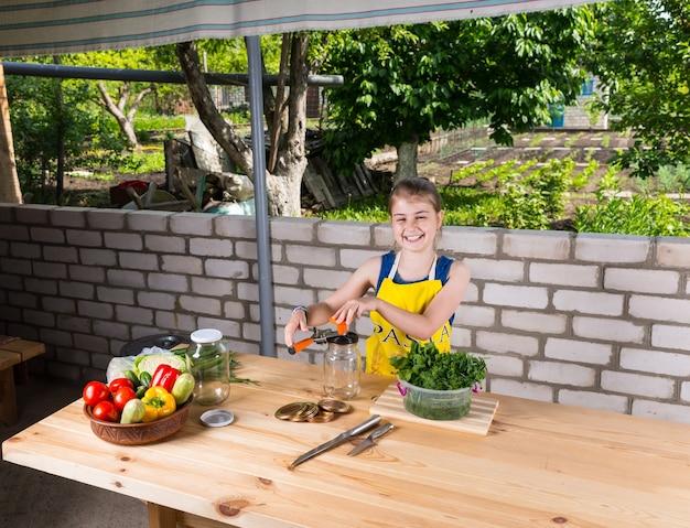 Jeune fille joyeuse et vivace mettant en bouteille des légumes frais sur une grande table extérieure en bois regardant la caméra avec un sourire rayonnant