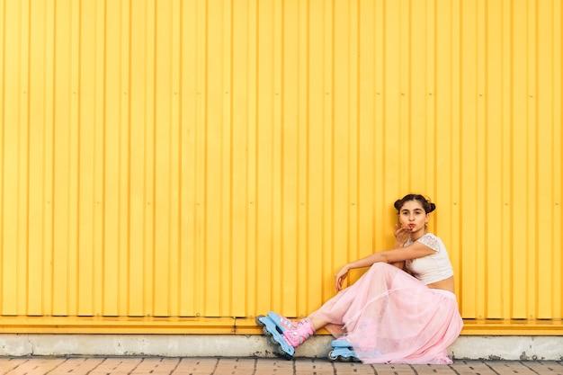 Jeune fille en jupe rose et patins à roulettes est assise sur le trottoir sur fond blanc