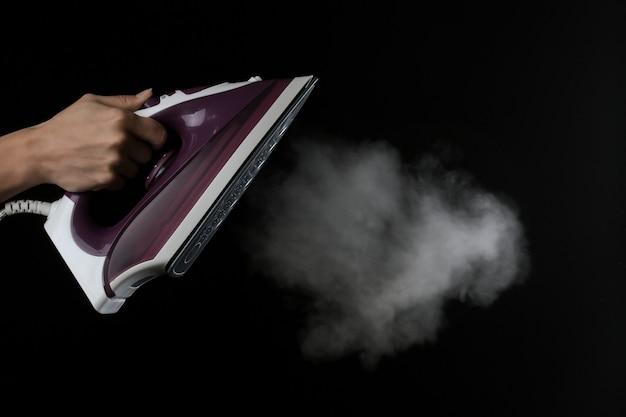 La jeune fille laisse échapper la vapeur du fer lilas sur fond noir. repasser des vétements. appareils électroménagers.