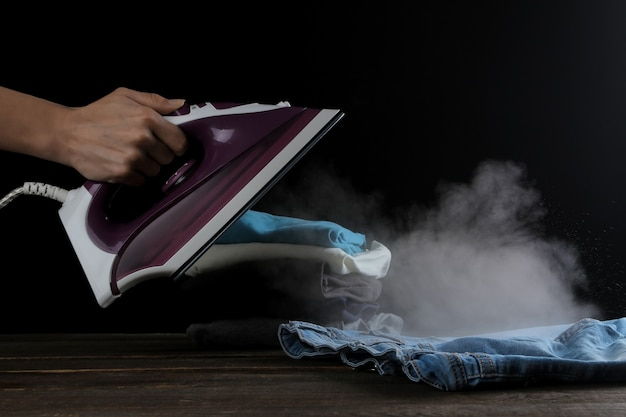 La jeune fille laisse la vapeur du fer lilas sur les vêtements sur fond noir. repasser des vétements. appareils électroménagers.