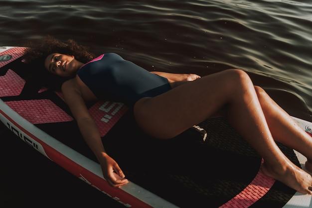 Jeune fille latine couchée sur le surf dans l'eau.