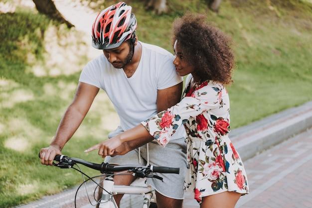 Jeune fille latine enseigne à son petit ami à faire du vélo